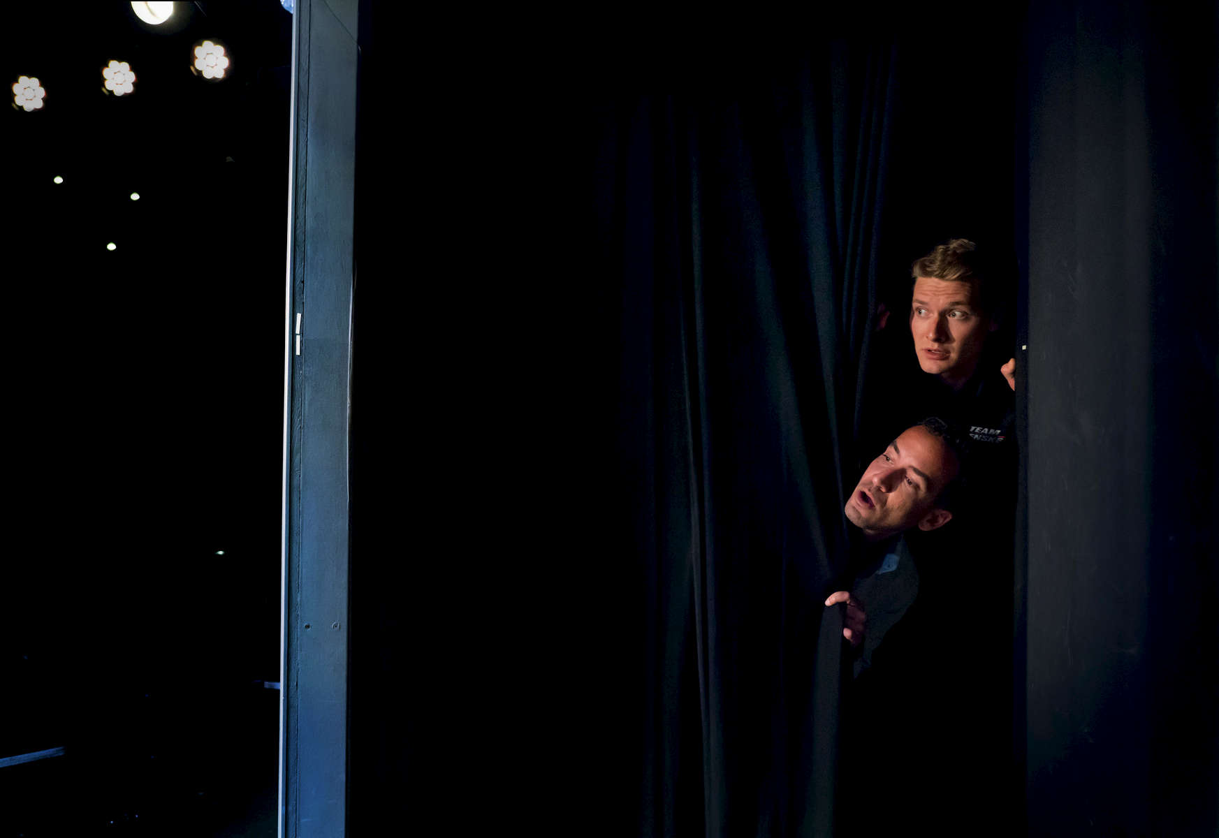 Indy 500 race champion Josef Newgarden, top, and ESPN {quote}Hang Time{quote} host Sam Alipour, peek out from behind a side stage curtain at The Second City Theater in Chicago.