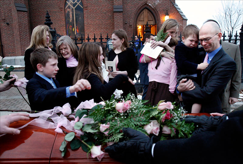 Carolynne's family places roses on her casket after the funeral. Friends and family dressed in pink, her favorite color.