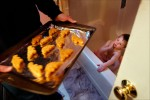 At EJ's request, Rich brings the dinosaur-shaped chicken nuggets into the bathroom where EJ can see them.
