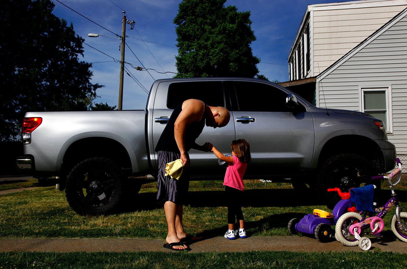 Tony and Ainslee, 2010Tony Grell, who's in the Coast Guard, inspects his 4 year-old daughter Ainslee's hurt finger outside the home he grew up in across from the Norfolk Naval Station.