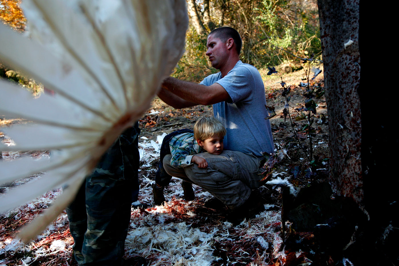 Jim Salmons, a neighboring farmer, helps clean turkeys while his son, Howard, 3, sits with him. {quote}I think it's good for him to come up and learn,{quote} Salmons said.