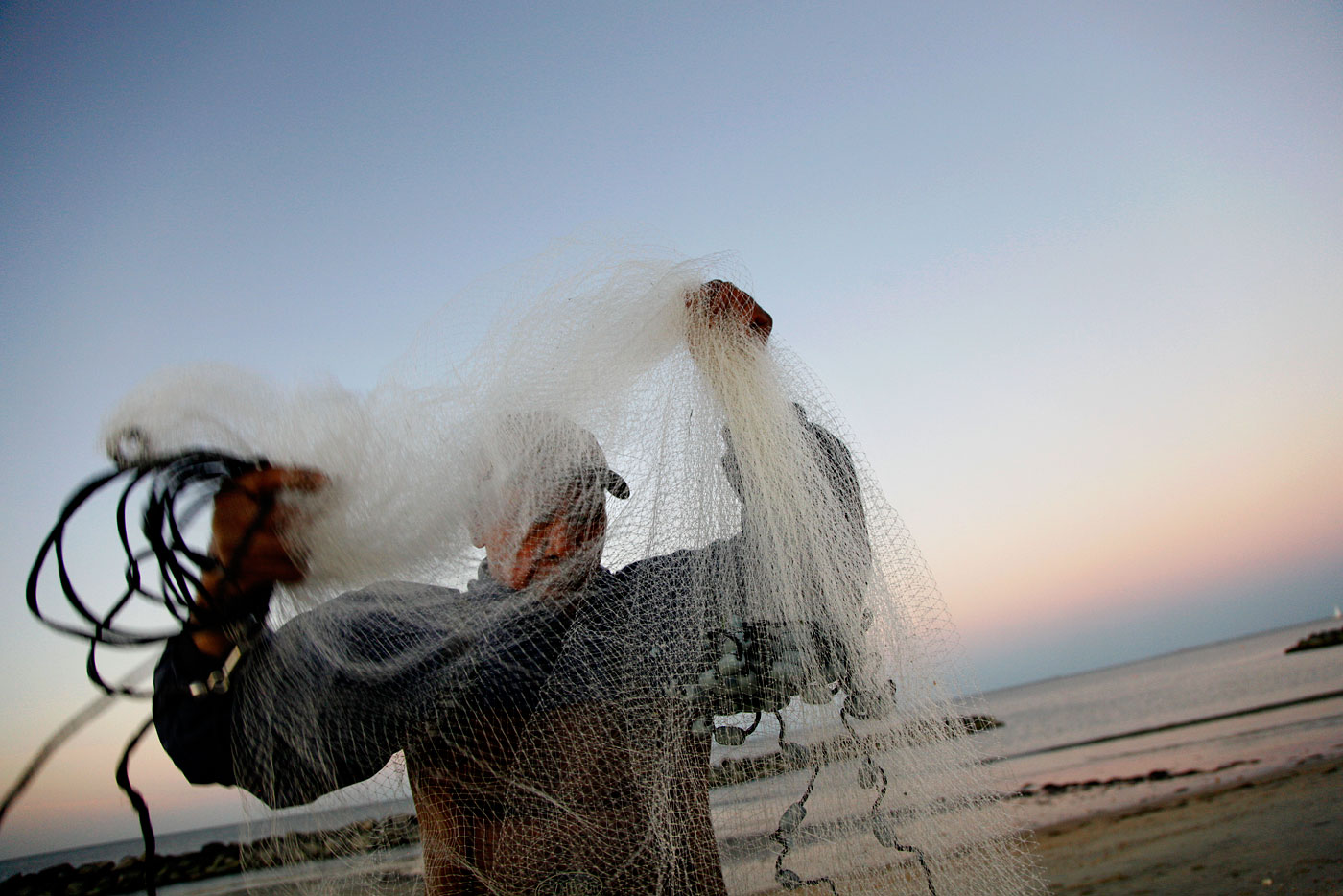 Andy Muyano stretches the cast net to release the mullet he caught while fishing in Ocean View.