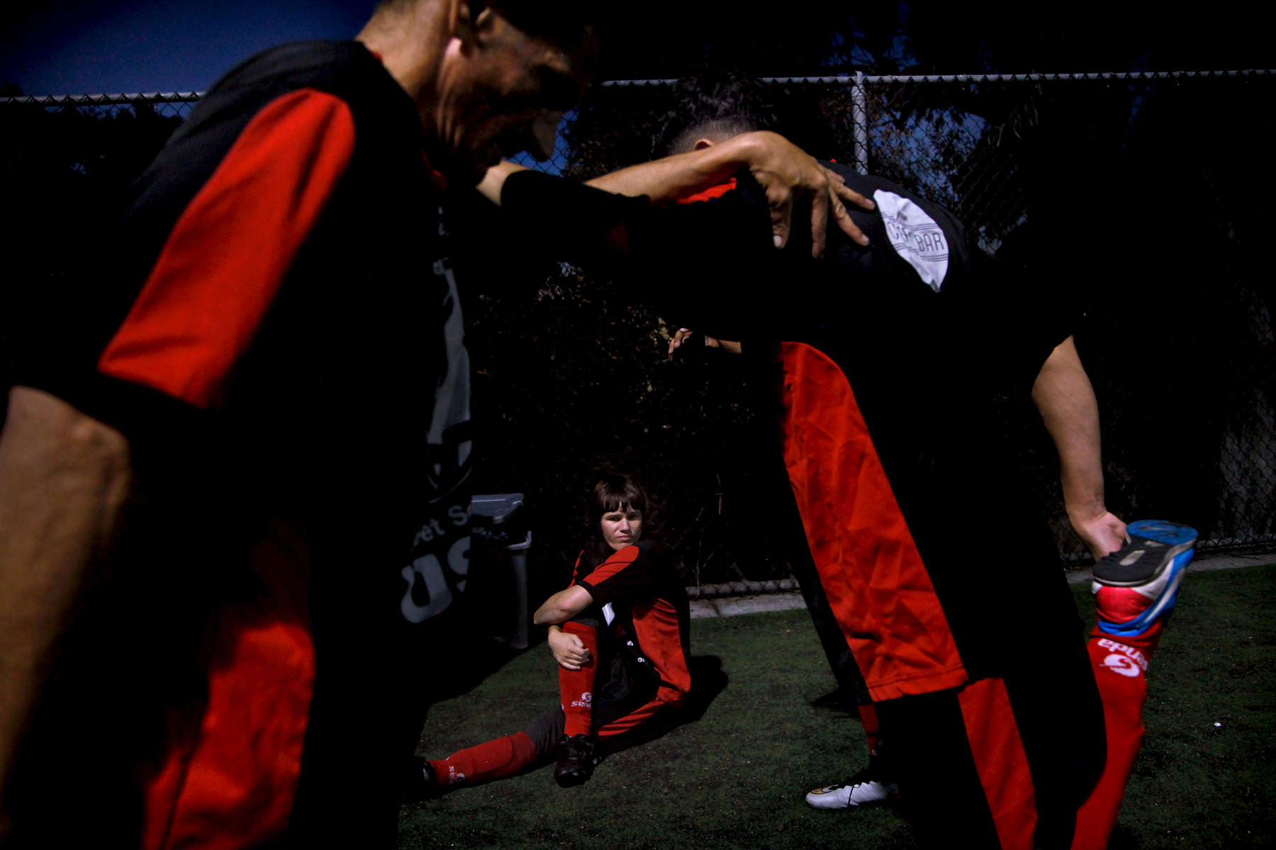 Isabella (center) and her teammates stretch before a Street Soccer game in San Francisco, Calif., on Thursday, October 22, 2015. Isabella describes the team as {quote}like the family you want to have.{quote}(Photo by Preston Gannaway © 2015)