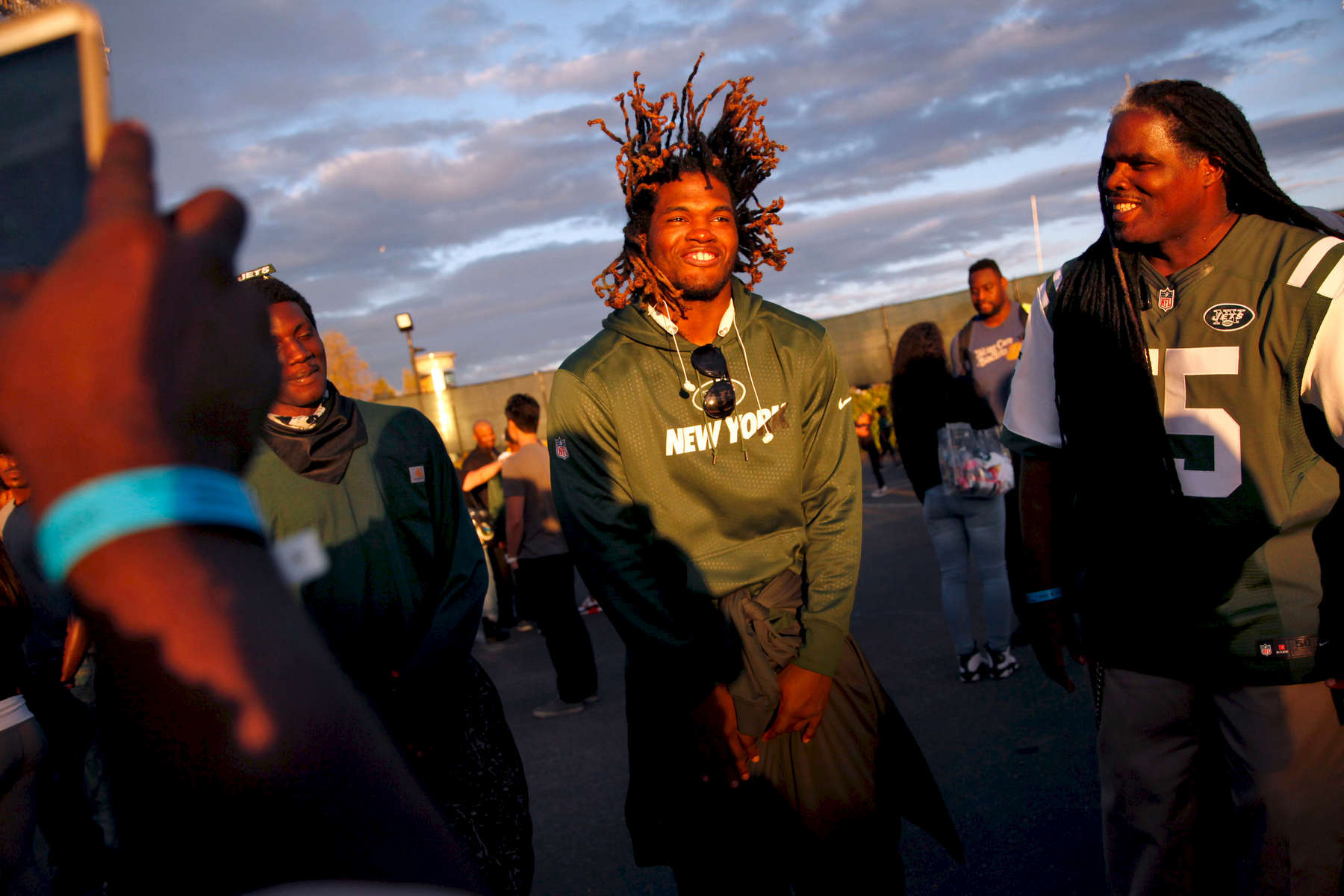Jets outside linebacker Lorenzo Mauldin tosses his dreads back while joking around with his family, including his brother Willie (left) and dad (right) after Sunday's game against the Oakland Raiders. Mauldin grew up in various foster care homes and reunited with his dad when he came to town for the game. Preston Gannaway for The New York Times