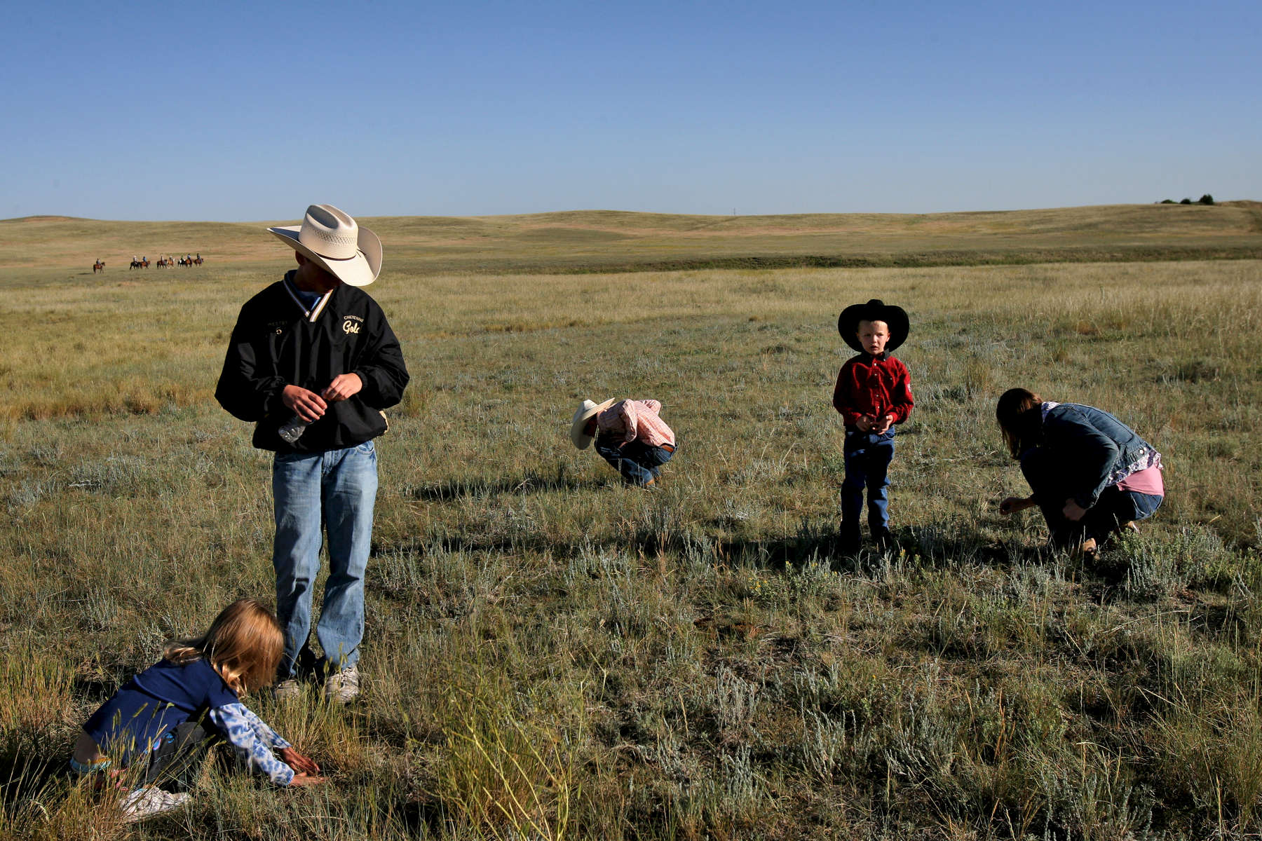Kids entertain themselves by catching grasshoppers in the pasture while cowboys head down the hill for the Cheyenne Frontier Days big cattle drive in Cheyenne, Wyo.