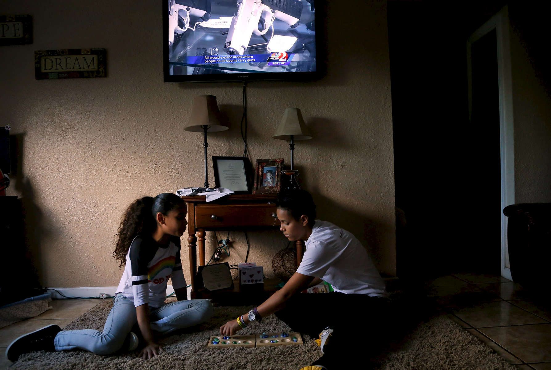 Pulse survivor Kaliesha Andino, 19, (right) and her sister Kinnie, 10, play a game at home six months after the shooting in Orlando, Fla., on Monday, December 12, 2016. Behind them a news report airs on a bill to loosen restrictions where people can openly carry firearms.