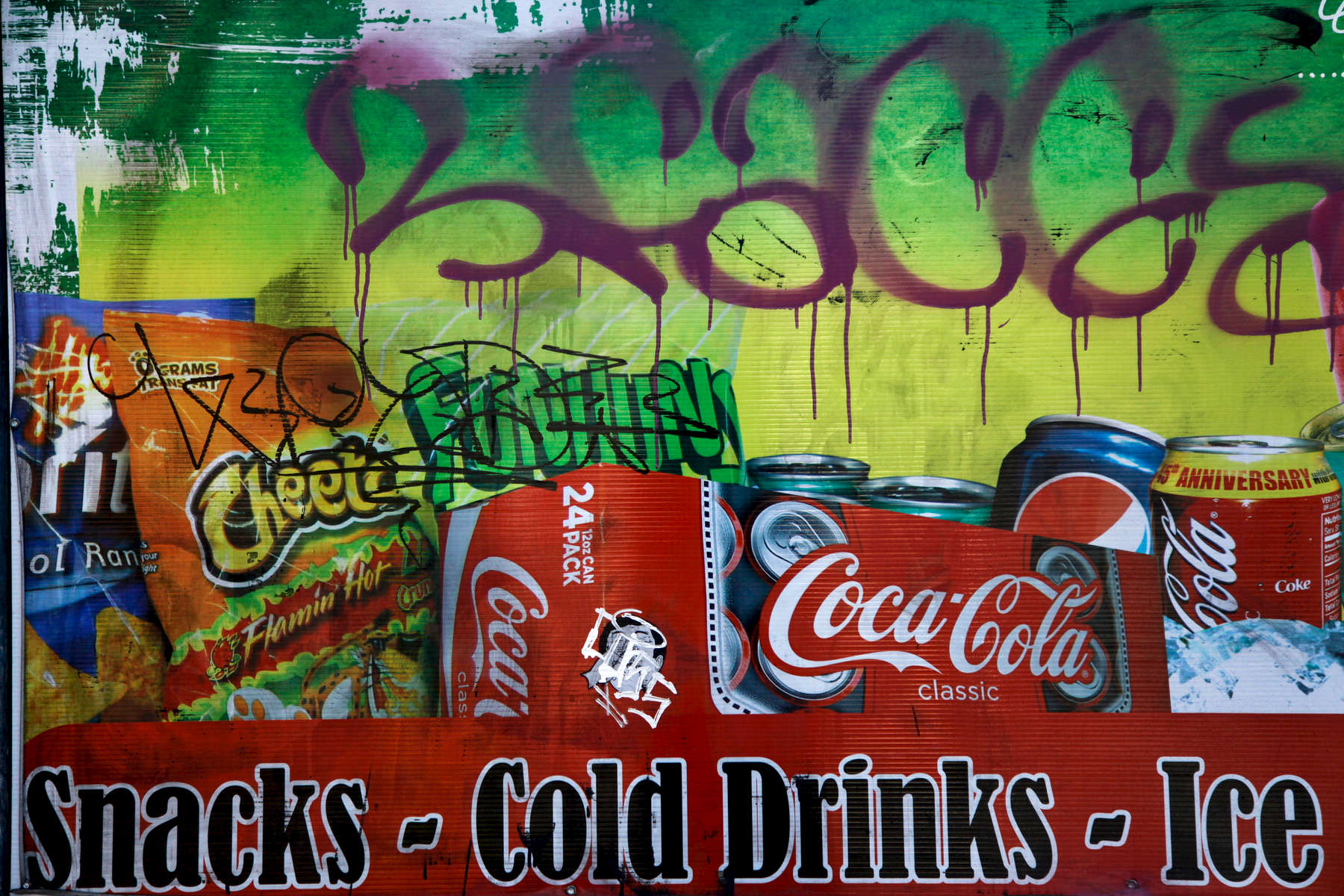 An advertisement on the side of a corner market in West Oakland. Much of Oakland is considered a food desert: a low-income area where most residents live a mile or more away from a  supermarket. Many residents without access to transportation are forced to buy their food from nearby liquor stores and convenience stores. (Photo by Preston Gannaway © 2016)
