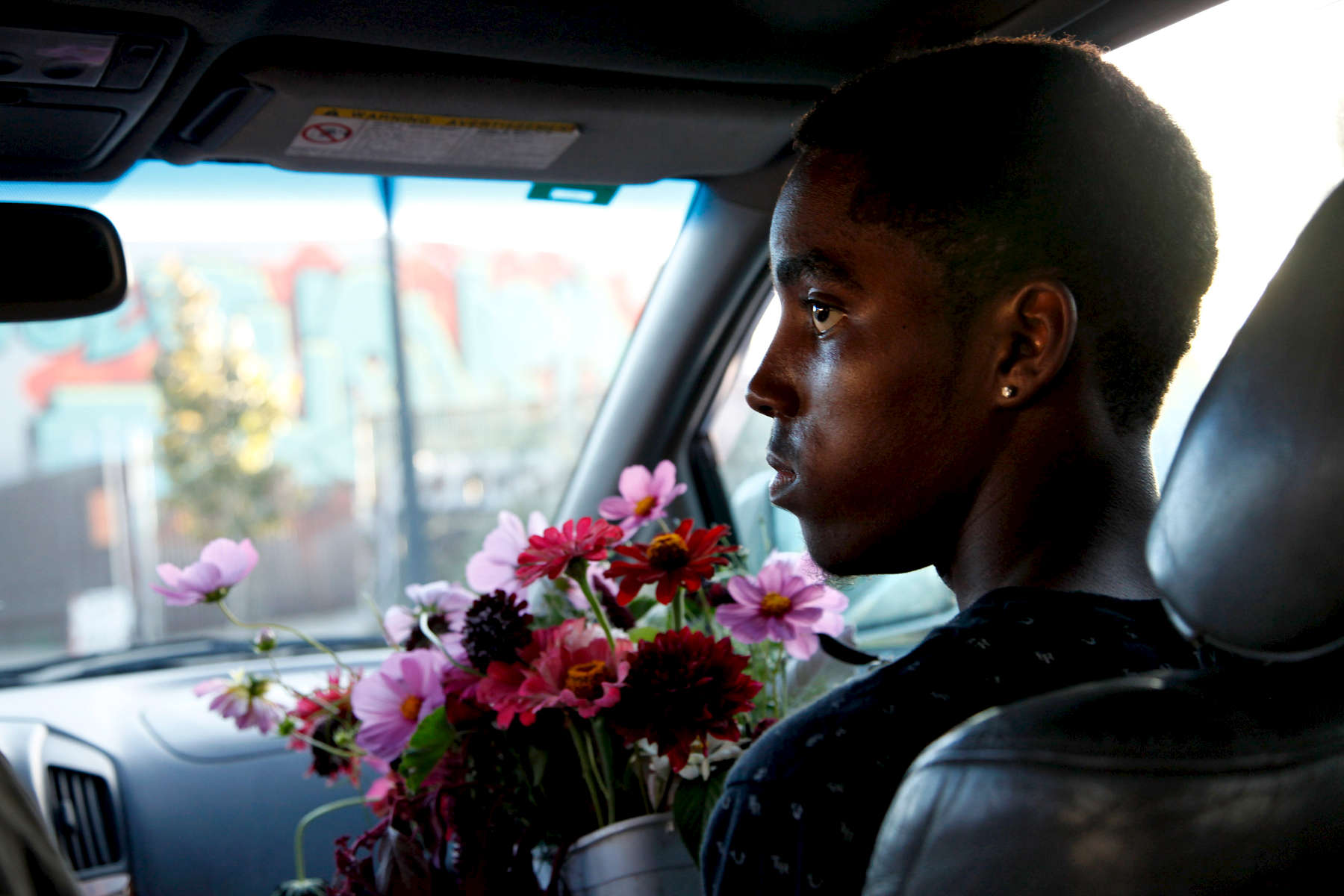 "Mekhi Brown, 15, holds flowers to be delivered to a local restaurant. Farm manager Jon Price ran a farm in Sacramento before moving back to the Bay Area to work with the interns at WOW. ""There's so much value. It's really therapeutic caring for living things."" (Photo by Preston Gannaway © 2016)"