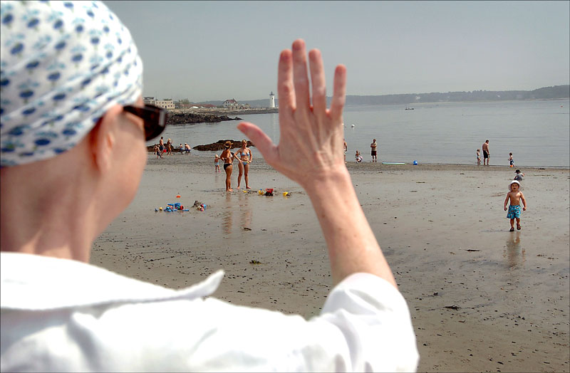 Carolynne waves while watching EJ play at the beach on New Castle Island. Family trips inspired Carolynne to continue with her treatments in hopes of being around for another summer.
