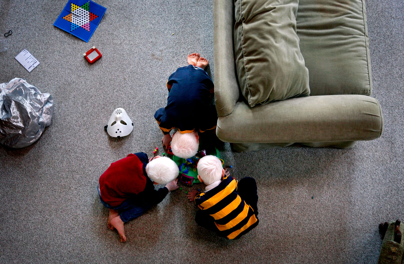 Micah (bottom right) plays with his brothers on his first morning at the Andersons' home in Isle of Wight, Va. Both Elijah and Paul were adopted at age 4. The brothers, who are not biologically related, are often mistaken for triplets.