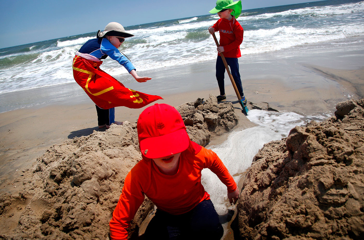 Paul, Elijah and Micah build a sandcastle during the Andersons' family beach trip to the Outer Banks in Corolla, N.C. To protect themselves from the sun, the boys have to keep their skin covered.