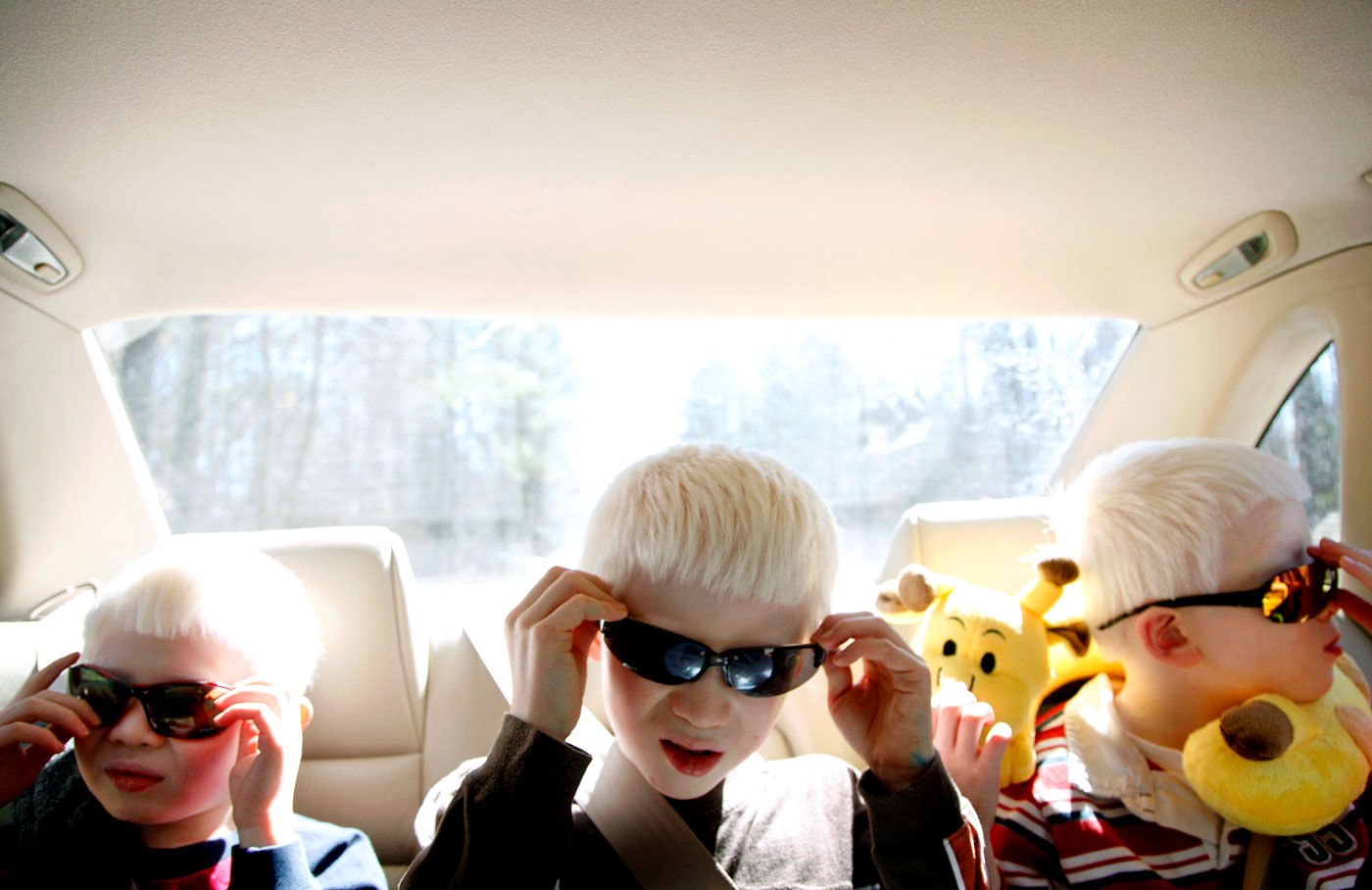 Micah, 9, Elijah, 10, and Paul, 8, put their sunglasses on as they head to a homeschool science class. People with albinism are sensitive to bright light and have low-vision issues.