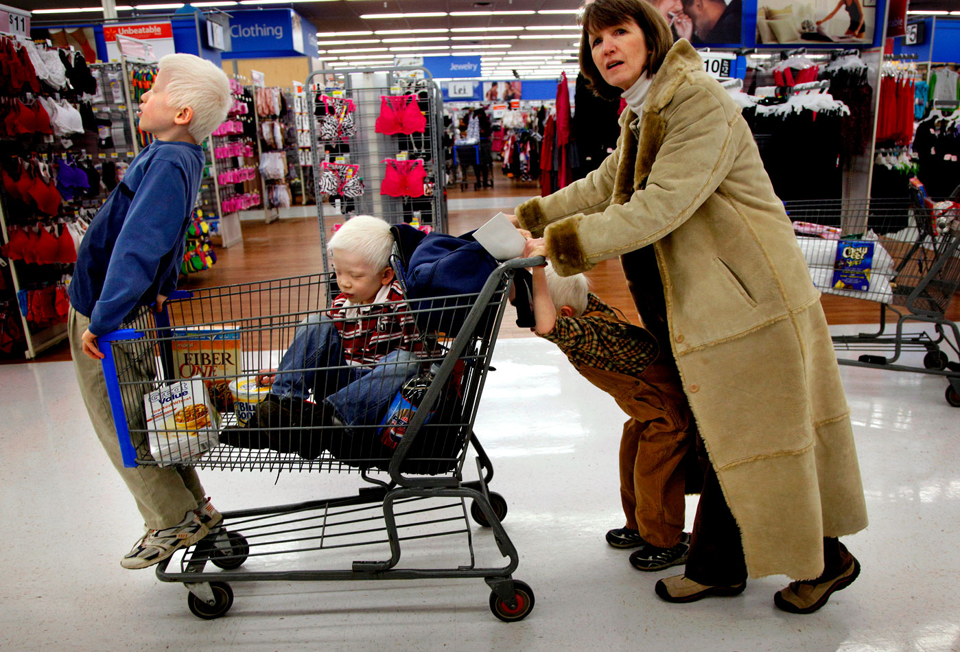 Elijah, Paul and Micah hang onto the cart as the family shops at Wal-Mart.