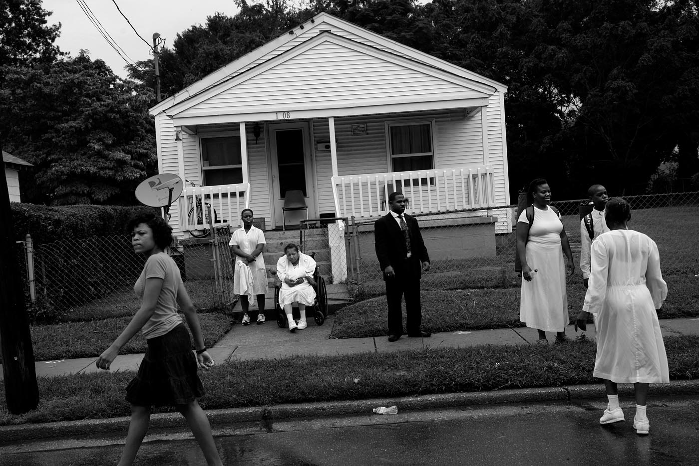 A few people linger after the crowds disperse following the mass baptism for the United House of Prayer of All People in Newport News, Virginia. Busloads of church-goers are brought to the neighborhood each year for the event.