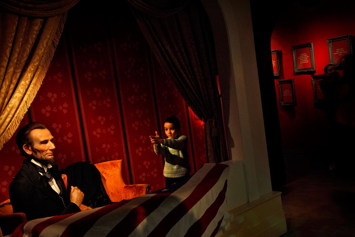 A boy plays around a wax replica of President Abraham Lincoln sitting in Ford's Theatre at Madame Tussauds in Washington, D.C. on Sunday, January 15, 2012.