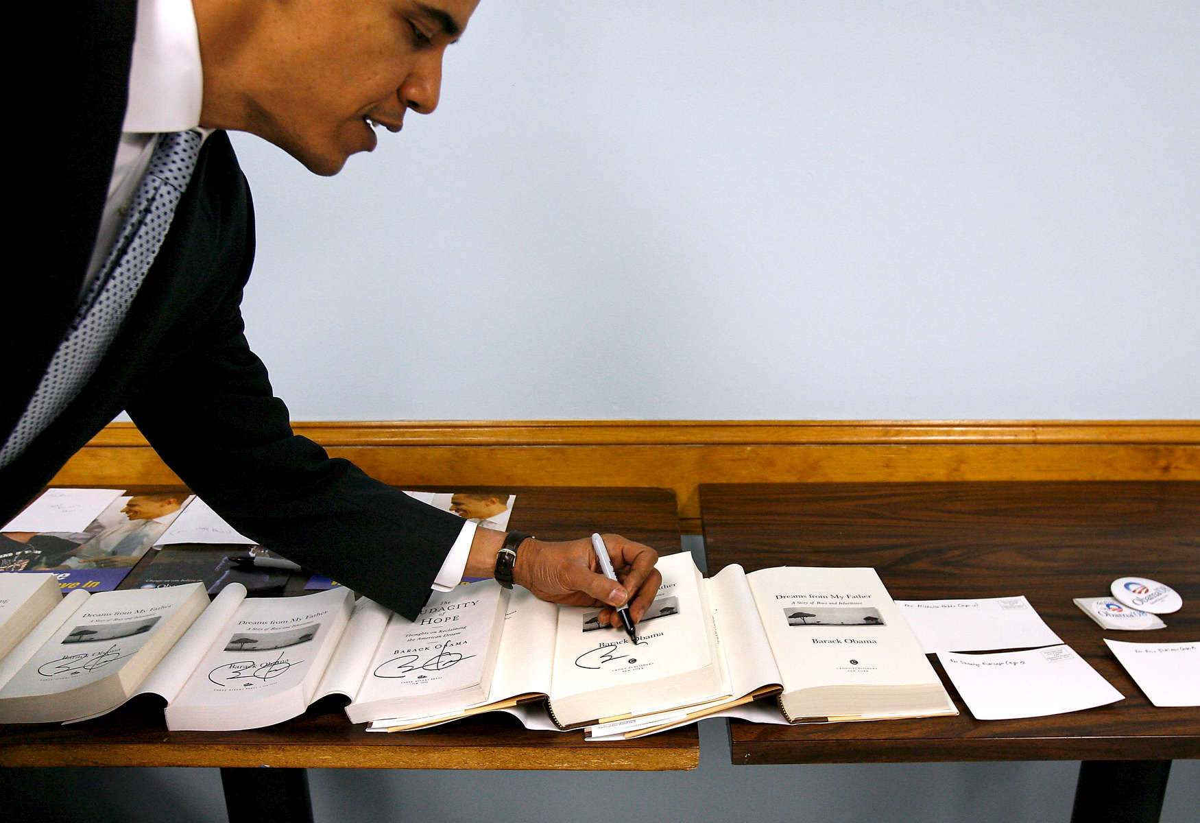Presidential candidate Barack Obama autographs a row of books laid out by campaign staffers for supporters after an event at the Rochester American Legion Post No. 4. in December 2007.