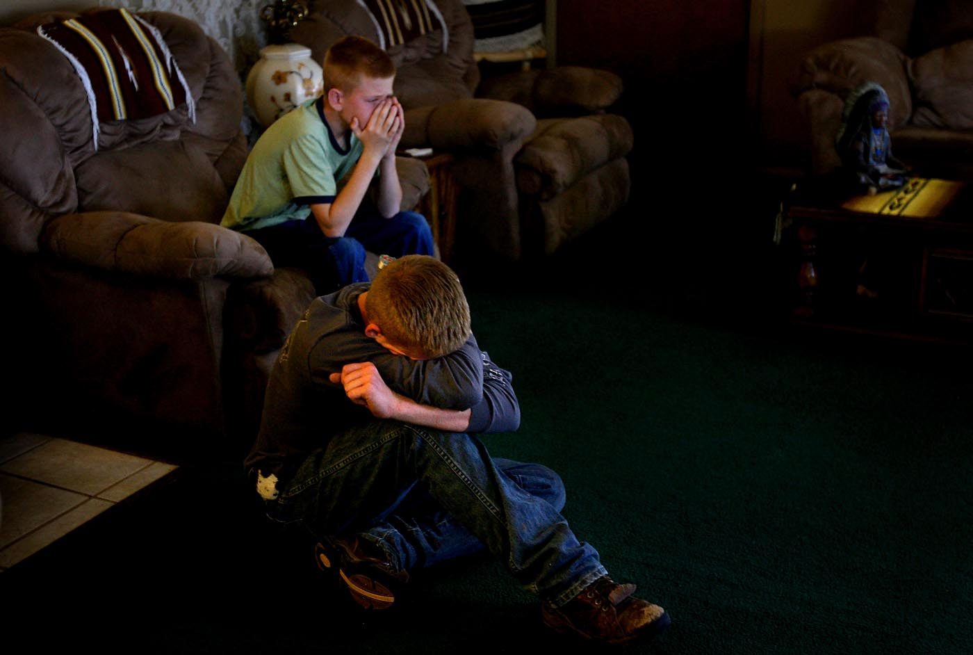 Jake, 11, and Cody Schwartz, 15, watch the news at their grandmother's house in Fowler, Colo. Their father, volunteer fire fighter John Schwartz, was killed the day before when the bridge he was driving on collapsed underneath him as he rushed to fight a fire in Ordway.