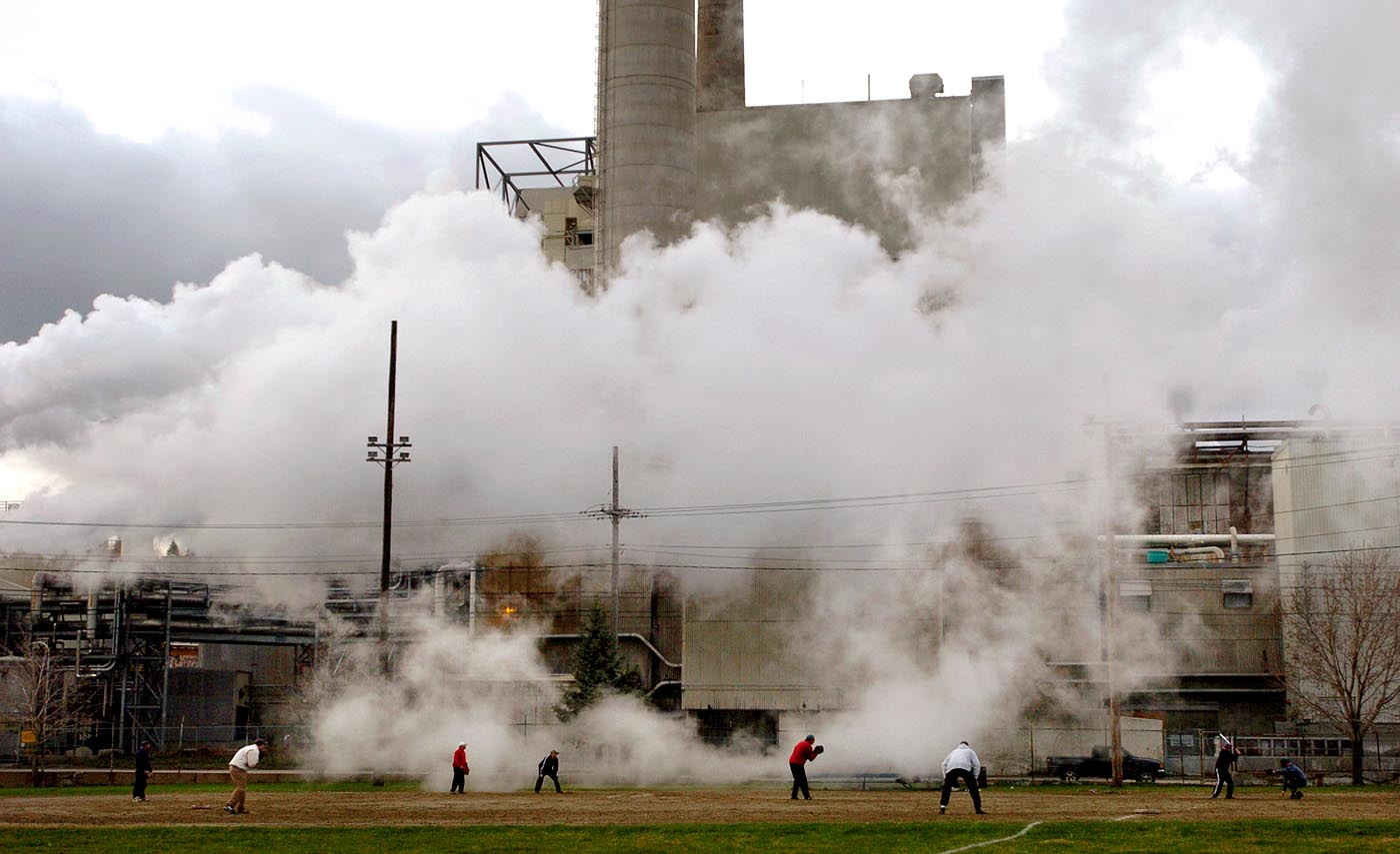 A recreational group from Milan, NH plays softball one evening as steam from the Berlin pulp mill surrounds them. 250 jobs will be lost when the mill closes.