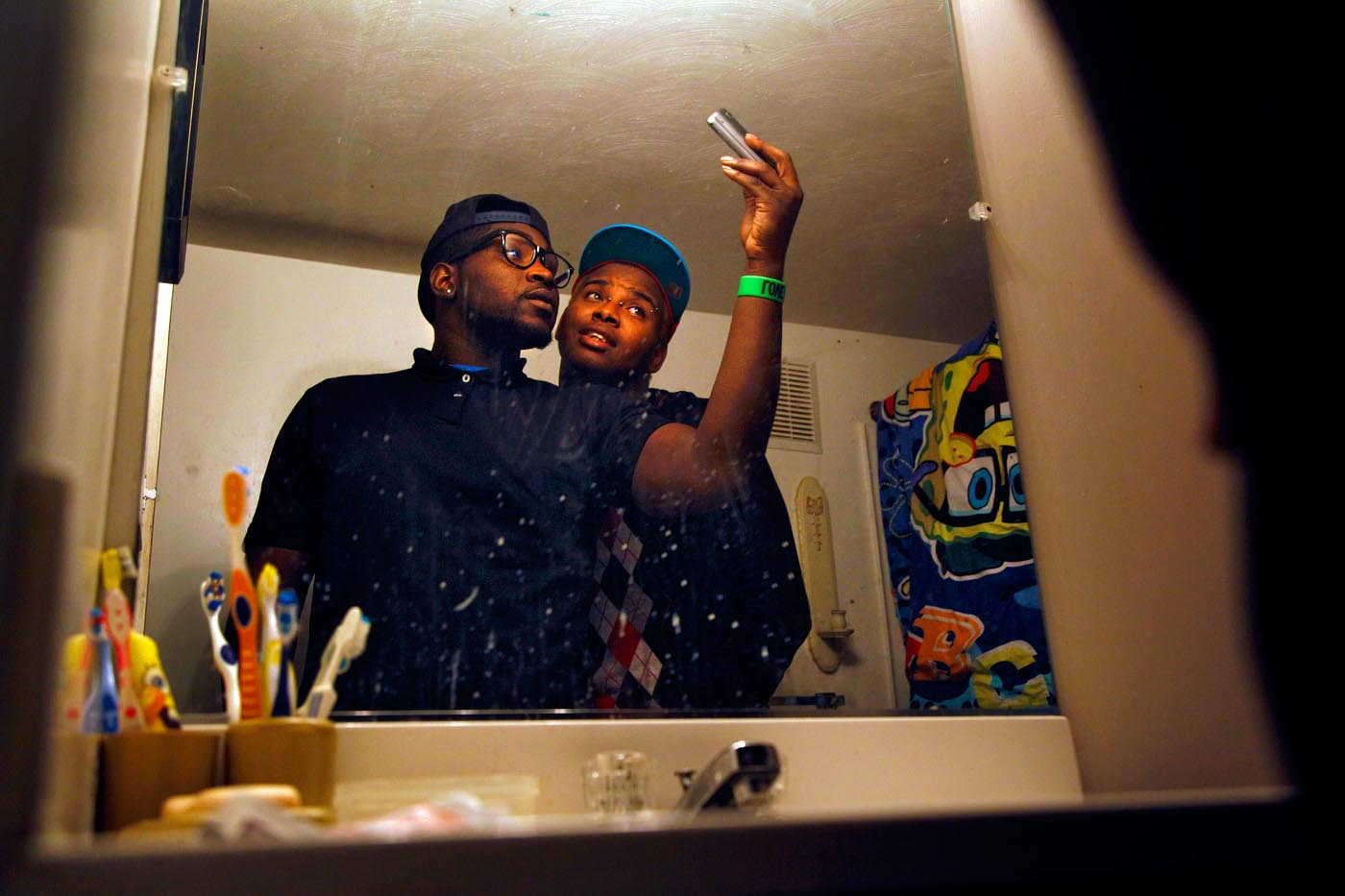 Teddy and his best friend Jamesie Johnson take self-portraits for Facebook in Jamesie's bathroom.