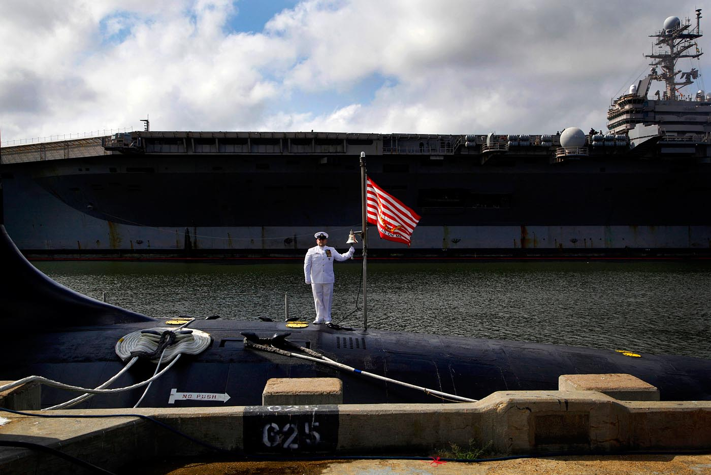 Chief Petty Officer Mark Eichenlaub stands on the submarine USS New Mexico while rendering the honors at the start of the Submarine Forces Change of Command ceremony at Norfolk Naval Station in Norfolk, Va., on Friday, September 7, 2012. In the background is the aircraft carrier USS Abraham Lincoln.