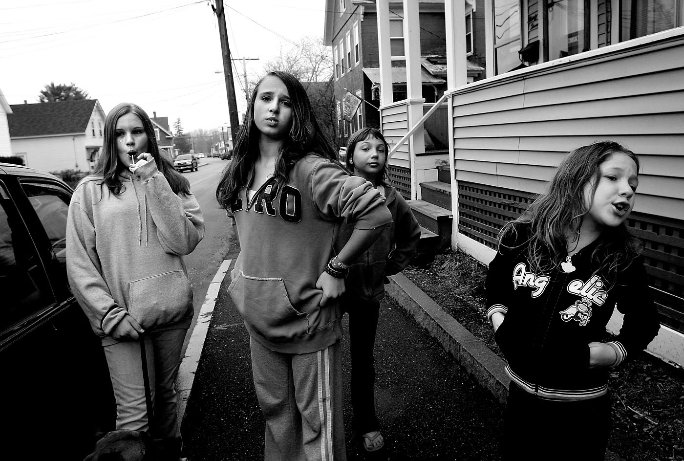 A group of neighborhood girls watch for the boys to return on their bikes while hanging out on Walker Street in Concord during spring vacation.