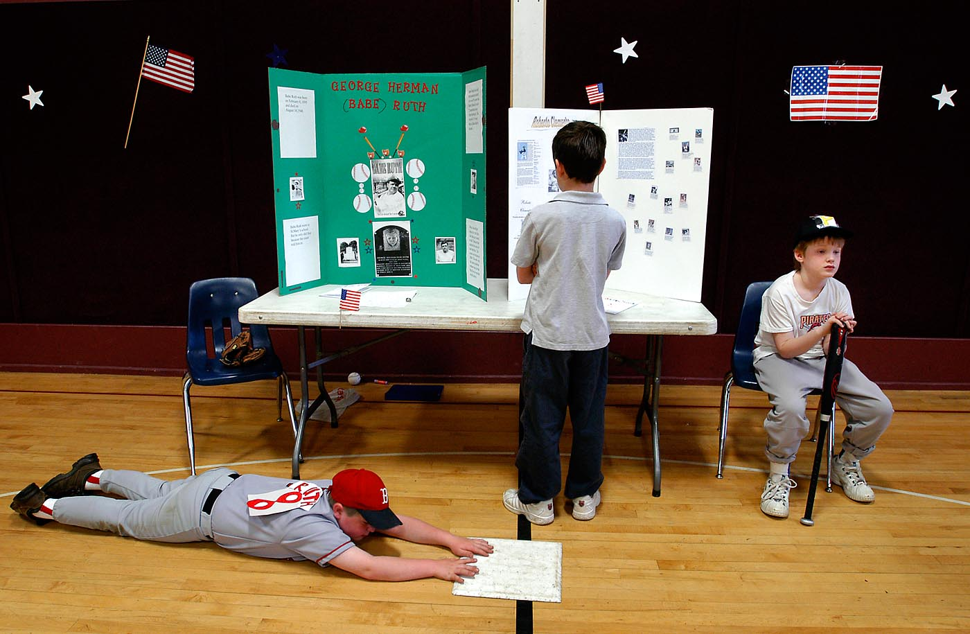 Posed as wax figures of baseball greats Babe Ruth and Roberto Clemente, third-graders Tom Hilton (left) and Adam Sylvester (right) hold still during Concord Christian's American Wax Museum. Fourth-grader John Holmes (center) studies their display boards.