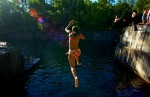 A swimmer leaps into the cold, blue water of Dorset Quarry in Vermont.  The quarry was given to the town after its owner ceased extracting marble from its depths.