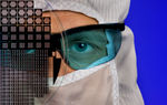 An employee wearing sterile protective clothing in a clean-room high-tech manufacturing facility looks through a digital optics wafer to give the product visual proportion and close-up detail. The human face, and eyes in particular, draw in readers and cause them to look longer than they otherwise might at photos of products photographed alone. The blue background was created using a blue gel over a flash. A thorough photo shoot should include a wide range of images, including a handful of striking photos that make readers pause and wonder.