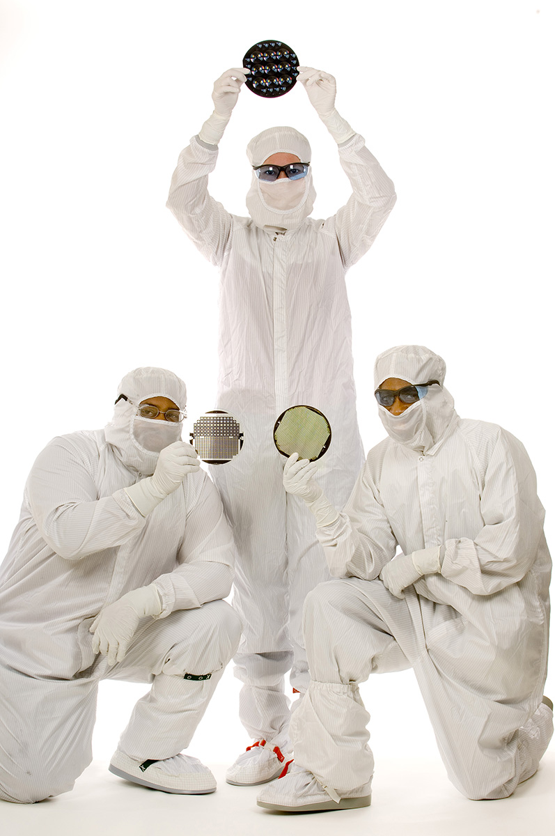 Three workers in high tech manufacturing operations hold samples of the digital wafers they manufacture in a sterile environment. The workers are holding flat, glass-like wafers that are about the size of a softball. All three employees are covered head to toe with white sterile uniforms. Photographing clean-room manufacturing processes or making environmental portraits of employees in sterile environments comes with specific challenges. 