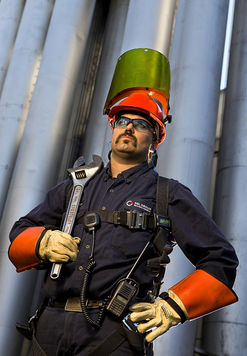 An industrial worker wearing a large visor and personal protective equipment (heavy gloves and safety glasses)  poses outside the manufacturing facility where he works. 