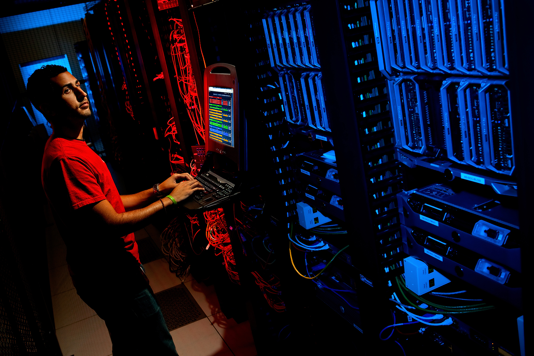 A data center employee types into a computer as he checks the calabrations of the data center's hard drives. Red and blue gelled lighting makes the bank of hard drives and connecting wires. Taking the photo from a high angle and adding blasts of blue and red highlights enhances the photo's visual interest, helps define the equipment in this otherwise dark and tiny room and expands the range and volume of images created during the shoot.