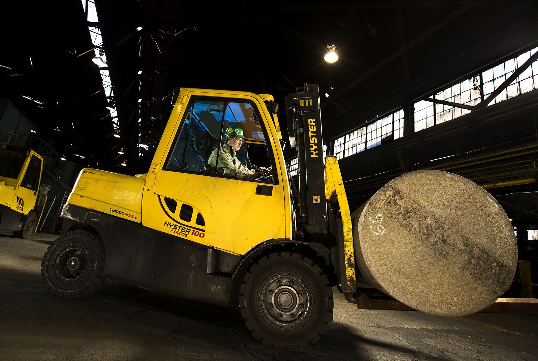 A man wearing a green hard hat and safey glasses drives a forklift in a manufacturing plant. Special lighting makes it possible to see the face of an employee as he operates a Hyster 100 forklift in a North Carolina manufacturing company. Without strategically placed lighting, the employee would be too dark to see. Too much lighting would wash him out.