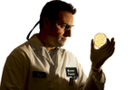 A man wearing a white lab coat and safety glasses looks at the spotted petri dish in his hand. He is shown in profile view, and viewers can see through the petri dish. He is well lit, but then falls to a dark shadow. 