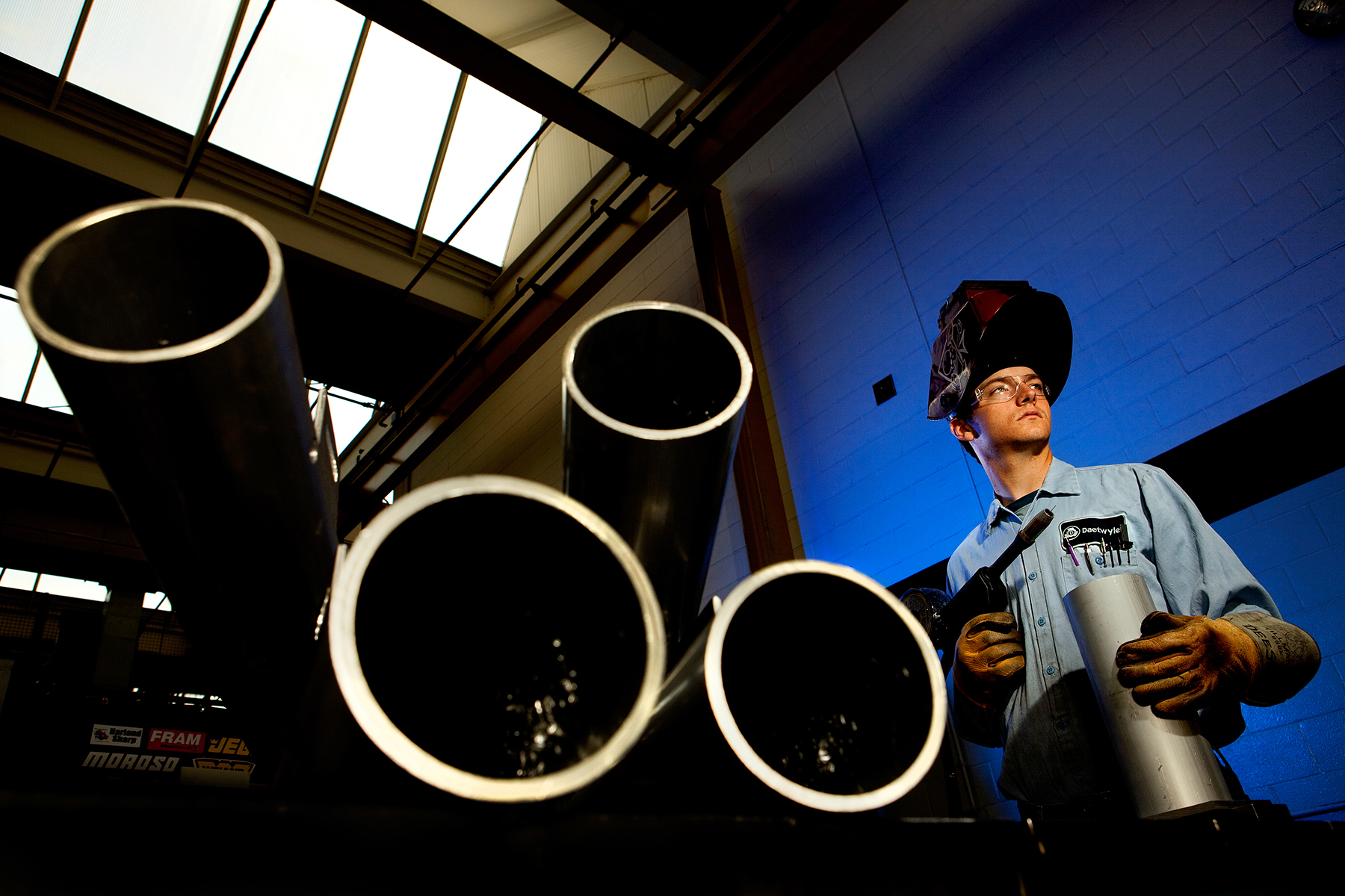 Blue gelled lighting makes a dynamic backdrop for a welder in a plant that manufactures equipment and products for the printing industry. The employee is wearing a welding shield or viser and is holding a blow torch. Four large pipes dominate the foreground of the photo.