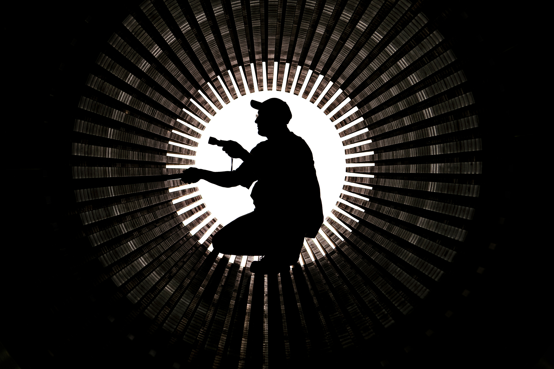 A black and white photo of a silhouetted man inside of the mouth of a giant turbine. The man is using a flashlight to inspect the blades of the turbine. As companies spend increasingly more money on continuous improvement processes that add efficiency to the manufacturing processes and ensure product quality and integrity, they're also finding it useful to photograph these corporate brand attributes for marketing and corporate communications purposes. In this photo of an employee of Siemens Energy's Charlotte Turbine-Generator Center inspecting the inside of a stator core, it's easy for prospective turbine customers to visualize the best practices that set Siemens above competitors.