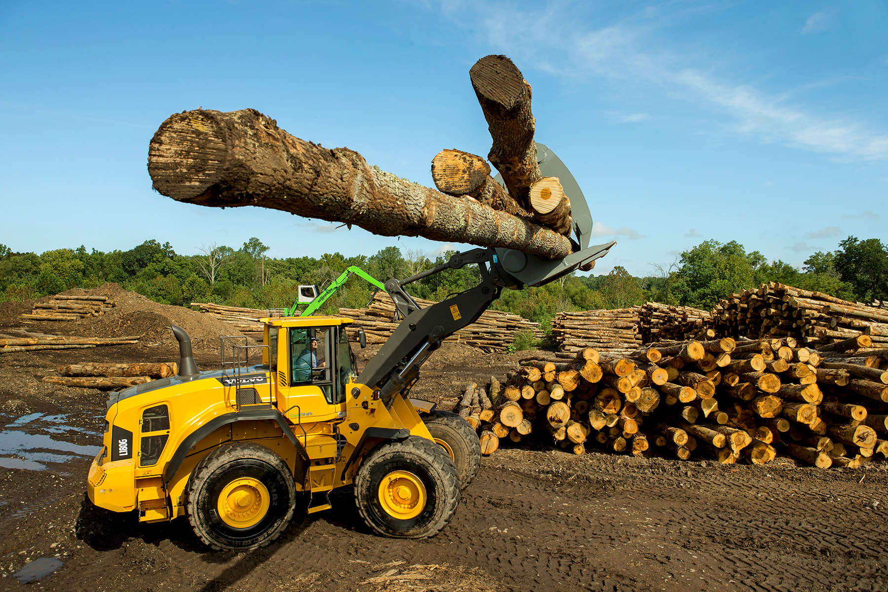 The driver of a Volvo loader drives four logs into the lot of a pallet company in North Carolina. Special lighting makes it possible to see the face of an employee as he moves logs inside the cab of the tractor/loader. Without purposeful lighting, the employee would be too dark to see.