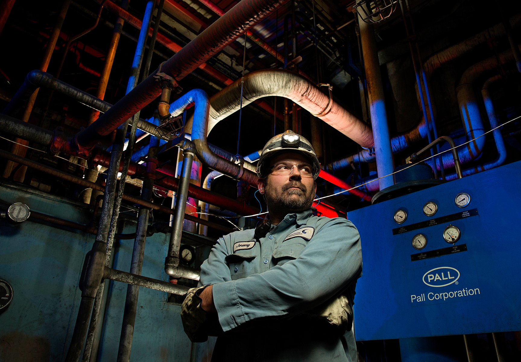 Manufacturing facilities are often dark and difficult to photograph properly. It's especially difficult to create an employee portrait in which the background behind him or her is also visible. At this manufacturing plant, we liked the graphic lines of the overhead pipes and duct work.  To create multiple photographic layers in the final image, we used a four-light system. The main Speedlight unit is positioned high and is zoomed to 105mm, which focuses the light on the worker and makes it seem as if the worker is being light from existing light from the factory. Three other Speedlight units are gelled with blue and red to illuminate the trail of pipes running overhead. The three Speedlights also help illuminate the machines that are part of the manufacturing operations.