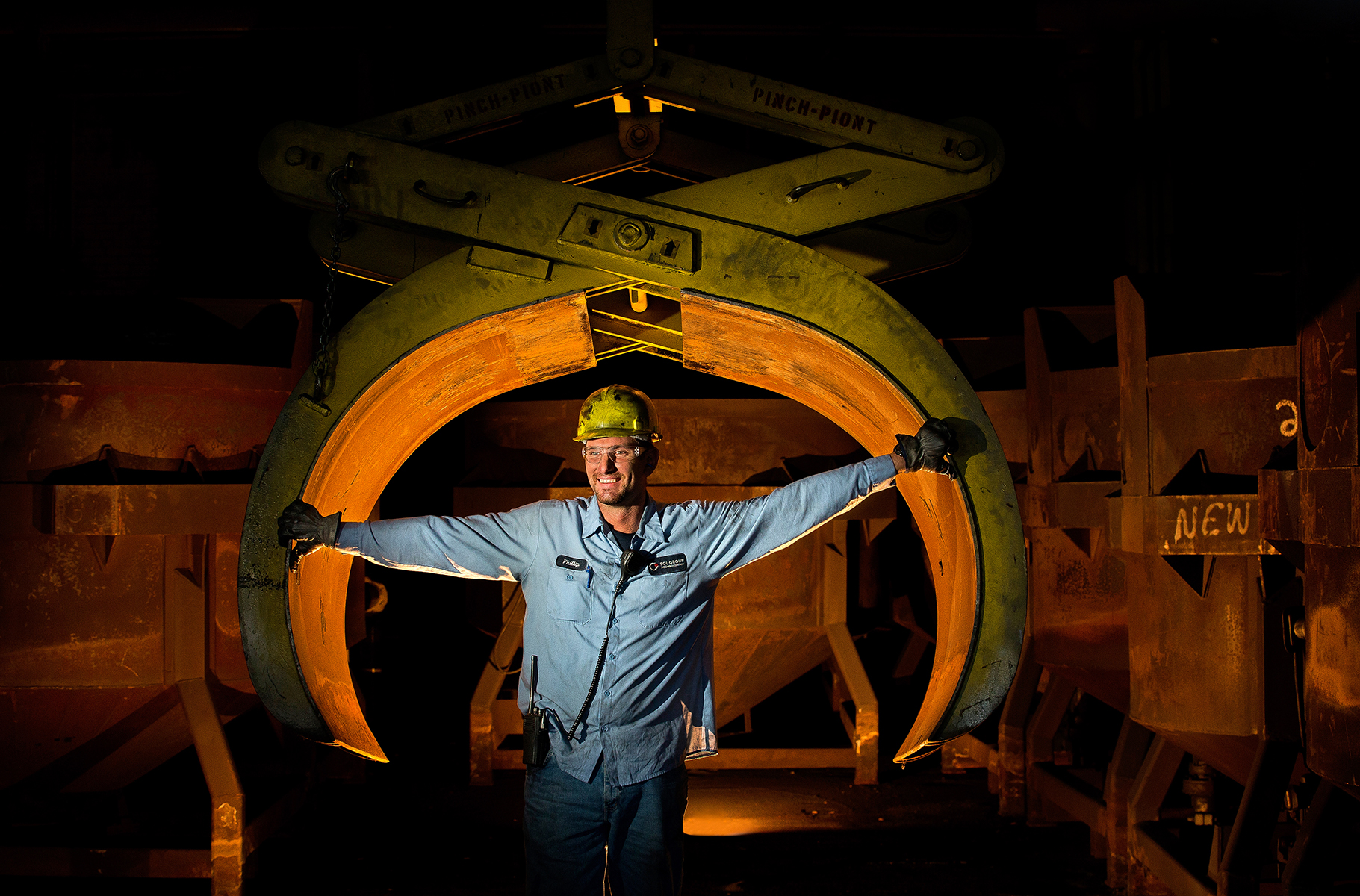 A man wearing a hard hat and heavy work gloves pauses to have his photo taken in front of Pinch-Point jaws used during manufacturing processes in a plant in Morgonton, NC. The giant pinch point jaws are lit from inside to focus attention on the employee.