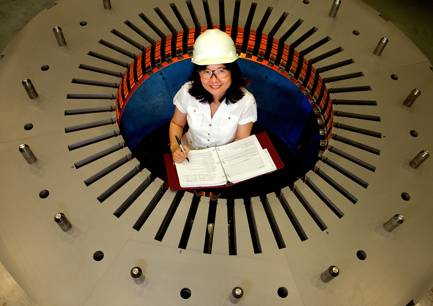 A female employee stands inside a giant turbine at a Siemens manufacturing plant. She is wearing a hard hat and is making notes.  