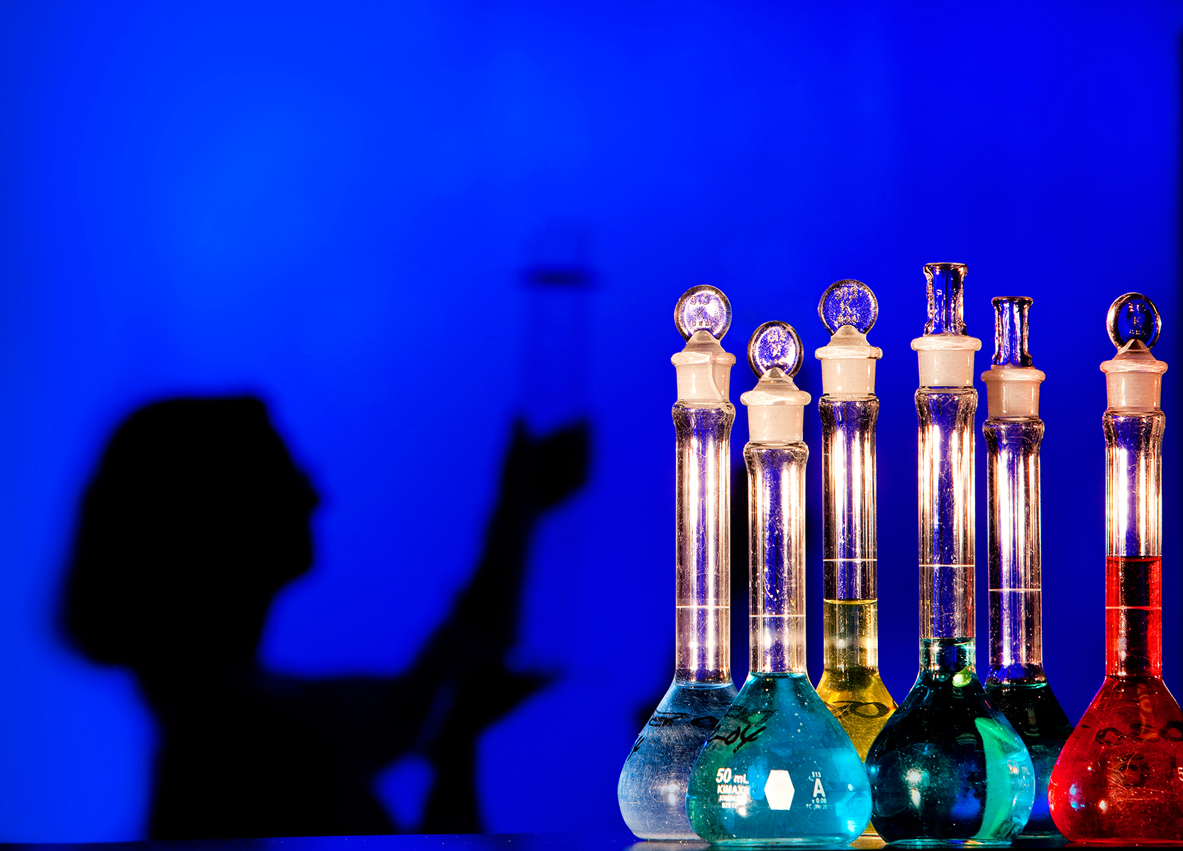 A silhouetted woman in the background of the image balances the bright liquid-filled lab flasks at a biomedical engineering firm that specializes in antimicrobial, odor control, and surface modification technologies. The photo has bright colors, including a cobalt blue background.