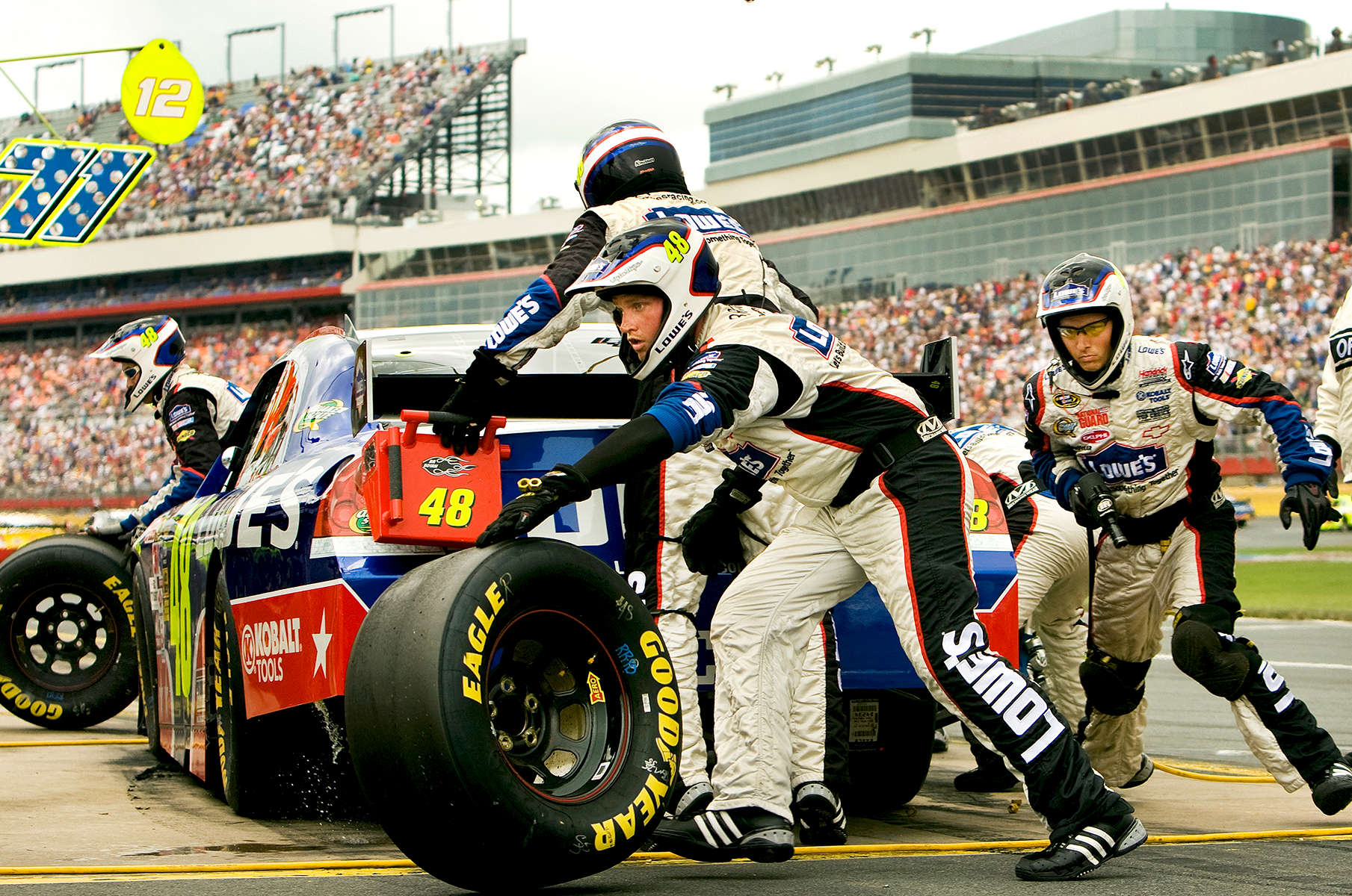 Members of Team Lowe's, the no. 48 Lowe's Chevy Monte Carlo driven by Jimmie Johnson, hustle during a pit stop in the 2009 Coca-Cola Classic 600 race at the Lowe's Motor Speedway, in Concord, NC. NASCAR Driver David Reutimann won his first Cup race during the rain-shortened event, held May 25, 2009. NASCAR's longest scheduled race went only 227 laps, or 340.5 miles, before officials ended it because of rain. The 2009 race was the 50th running of the Coca-Cola 600. Ryan Newman and Robby Gordon finished second and third respectively.