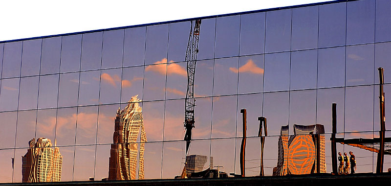 © Patrick Schneider PhotographyThe Charlotte skyline, shown here under construction, is reflected in the glass of a building.