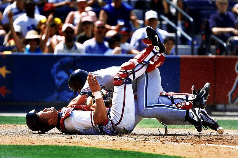 Florida Marlins Kevin Millar slams into Atlanta Braves catcher Javy Lopez scoring on a sacrifice fly at Turner Field