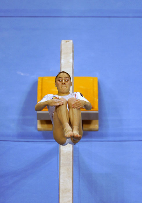 Gymnast Oana Ban of Romania does a backflip during competition on the balance beam during the 2004 Olympics