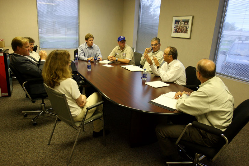 Team owner Jack Roush conducts a meeting with Carl and several team officials