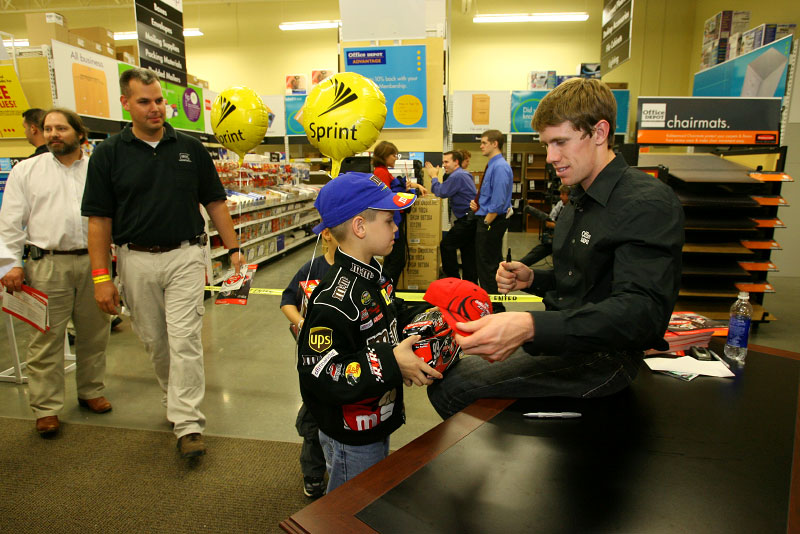 Carl signs an autograph for a young NASCAR fan who waited in a long line of fans at the Office Depot