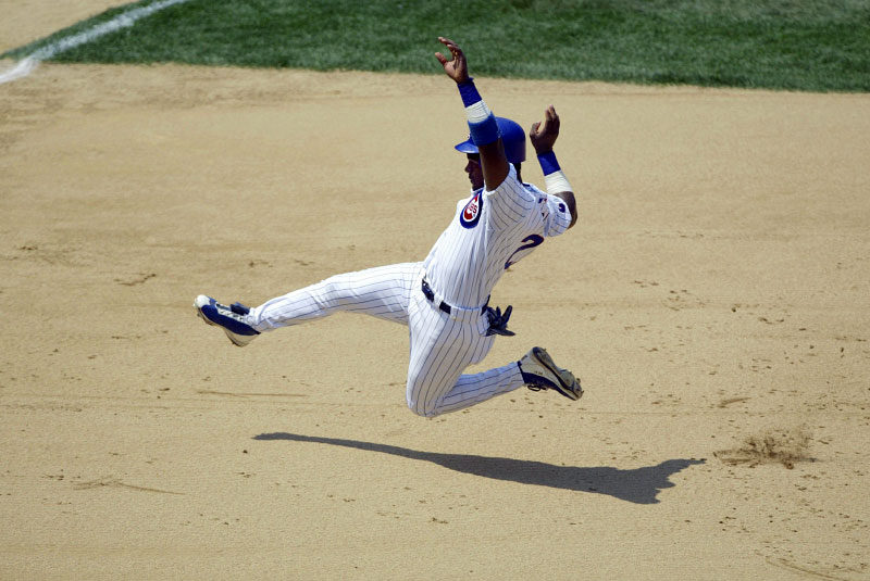 Chicago Cubs Sammy Sosa slides into third base against the Milwaukee Brewers