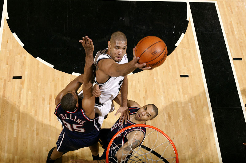 An aerial view of San Antonio Spurs Tim Duncan as he goes to the basket against New Jersey Nets Jason Collins and Kenyon Martin during the 2003 NBA Finals