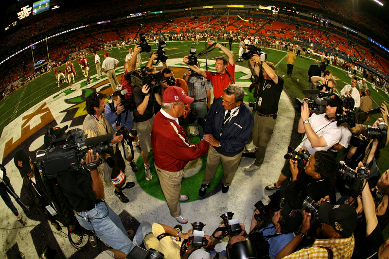 Fish eye view of Florida State coach Bobby Bowden on field shaking hands with Penn State coach Joe Paterno before the game surrounded by media