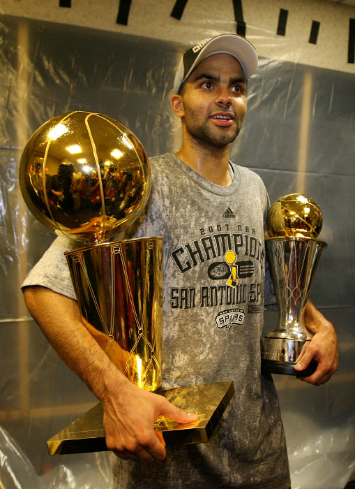San Antonio Spurs Tony Parker in the locker room with the Larry O'Brien trophy and the MVP trophy after winning Game 4 and the NBA championship against the Cleveland Cavaliers